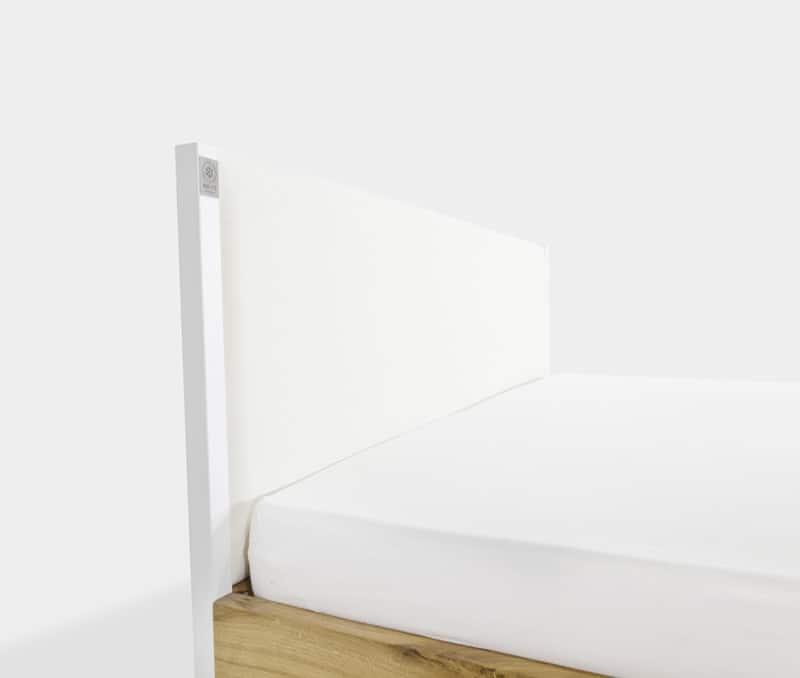 die massive Eichen-Rückwand des Bettes mit bespanntem Stoff aus Baumwolle