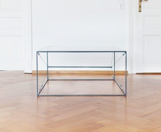 Ein klassisches Design, minimalistisch wie das Bauhaus Dessau. Filigraner Stahl mit eingefaster Glasplatte, kombiniert mit Stahlseilen. Der pulverbeschichtete Stahlcube trägt das Glas mit Leichtigkeit. Das Glas schwebt scheinbar über dem Boden.
